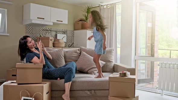 Thumbnail for Young Mother and Her Little Daughter Jumping on Bed. Funny Pillow Fight. Play Together and Enjoy the