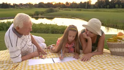 Little Girl Drawing with Grandparents.