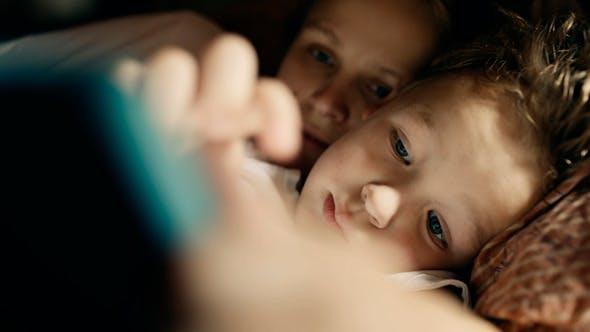 Thumbnail for Mutter und Sohn spielen auf tablet pc vor dem Bett