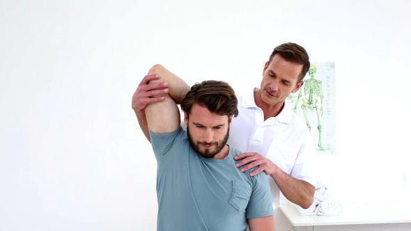 Physiotherapist Stretching Patients Shoulder