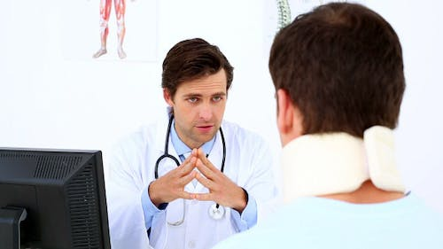 Doctor Speaking To Patient With A Neck Injury