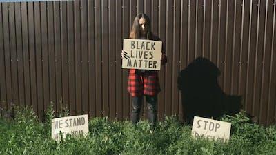 "Woman holds sign ""Black Lives Matter""."