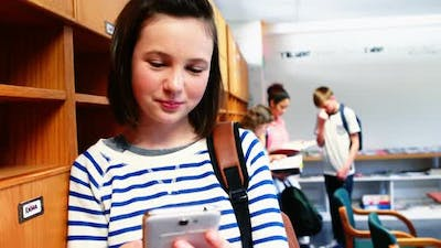 Smiling school girl using mobile phone in class room