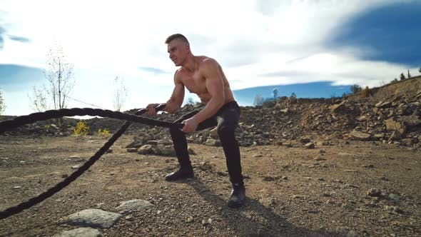 Thumbnail for Athletic male performs battle ropes exercise at sunlight