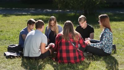 Young Christians Sitting in Circle and Praying