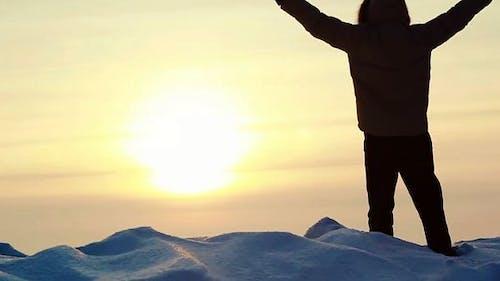 Mann posiert auf einem Gipfel bei Sonnenuntergang