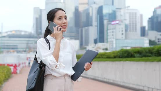 Thumbnail for Businesswoman talk to mobile phone and hold with laptop computer