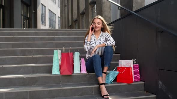 Thumbnail for Girl Sitting on Stairs with Bags Talking on Smartphone About Sale in Shopping Mall in Black Friday
