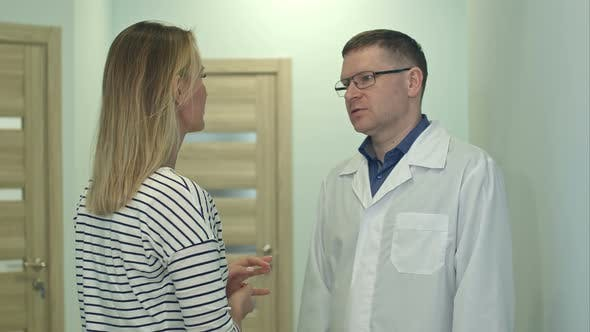 Thumbnail for Male Doctor Talking To Young Woman Patient in the Hospital Hall