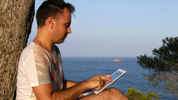 Thumbnail for Browsing Tablet Next to the Sea