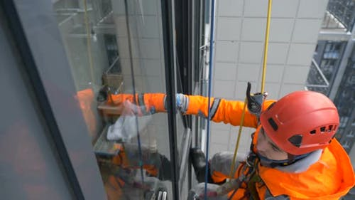 Equipped Window Washer in Helmet and Overalls Washes Glass with Screed at High Altitude of Building