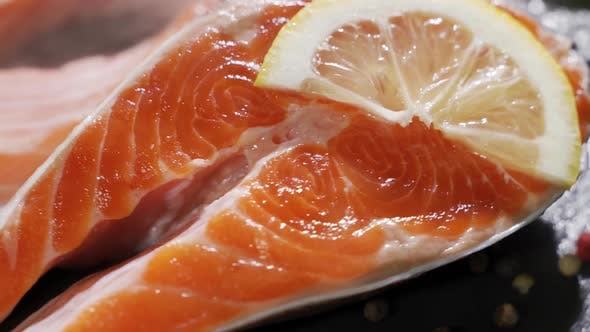 Cover Image for Fresh Piece of Salmon Placed on Cutting Board on Kitchen Table with Spices, Lemon