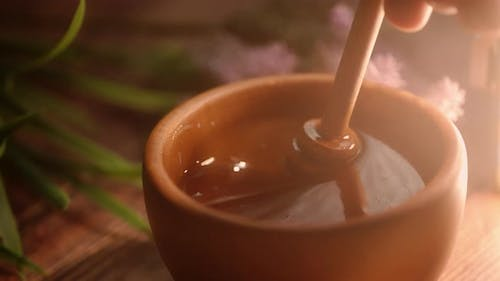 A Person is Dipping Wooden Spoon in Honey