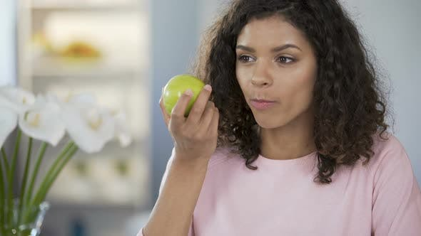 Thumbnail for Multiracial Beautiful Woman Eating Apple at Table, Daydreaming, Happy Thoughts