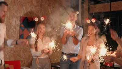 Happy Young People Are Kindling Sparkles in Christmas Night on Party and Cheering