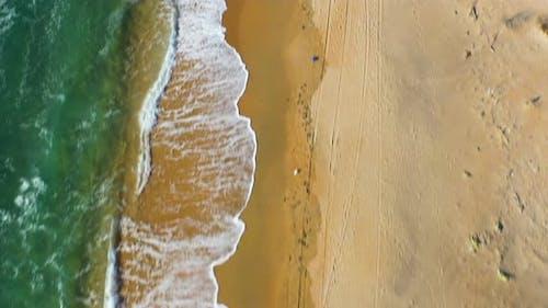 Drone flying toward horizon above sandy beach spit along sea in sunny day