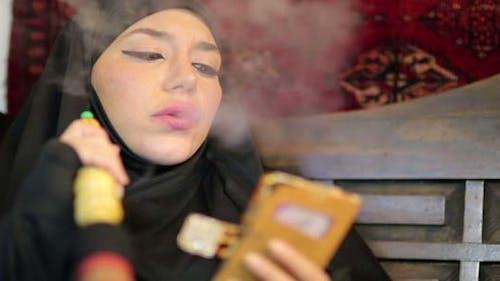 Woman With Chador Smoking Shisha and Using Mobile Phone