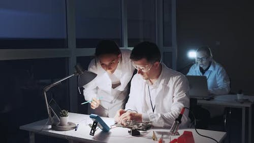 Mixed Race Electronics Engineers in White Coats Working on Motherboard Using Multimeter Tester
