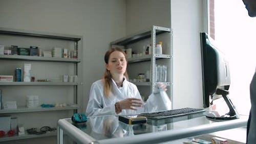 Customer Picks Up Order in White Package From Female Pharmacist at Pharmacy