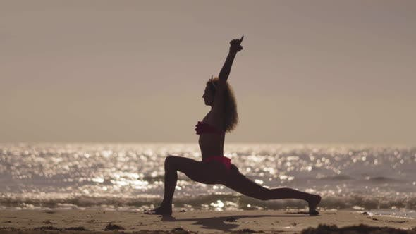 Thumbnail for The Girl Practic Yoga on the Beach at Sunset. Young Girl Doing Exercise at a Tropical Beach