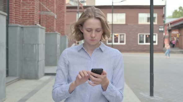 Woman Using Smartphone While Walking in Street