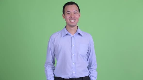 Thumbnail for Studio Shot of Happy Asian Businessman Smiling