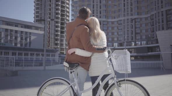 Thumbnail for Tall Man Hugs Pretty Blond Woman in Warm Jacket Standing Near Bicycle Looking on the High Building