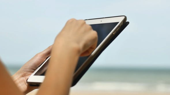 Thumbnail for Woman Using a Tablet On Beach