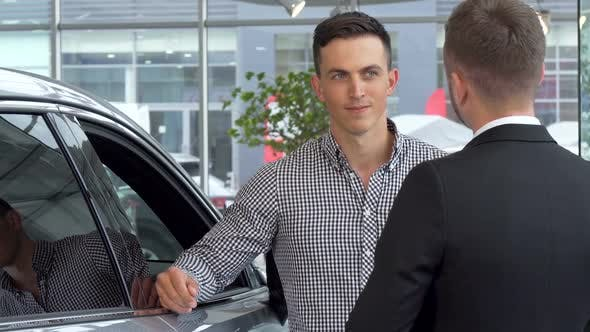 Thumbnail for Handsome Man Shaking Hands with Car Salesman at Automobile Dealership