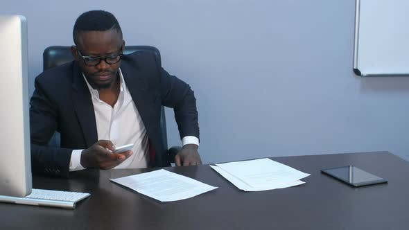 Thumbnail for Afro-american Businessman Texting Emails on His Smartphone Indoors