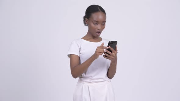 Thumbnail for Young African Woman Looking Shocked and Stunned While Using Phone