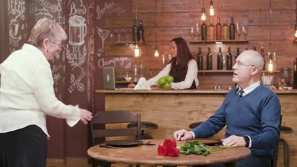 Senior Woman Arrives on a Date and Her Partner Gives Her Flowers
