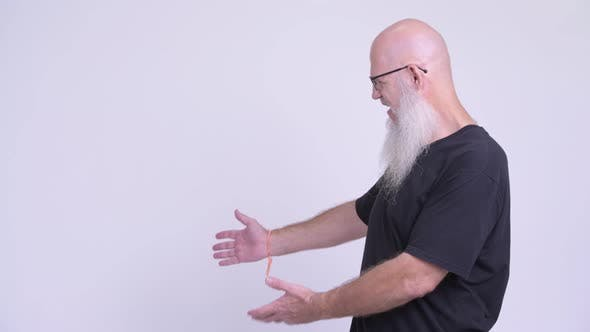 Thumbnail for Happy Mature Bald Bearded Man Smiling While Showing Something