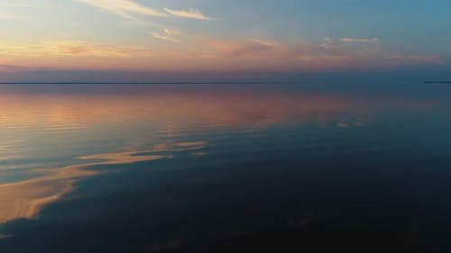 Aerial Drone Footage. Fly Over Calm Water To Sunset