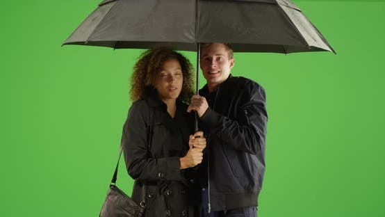 Thumbnail for Young multi ethnic couple holding umbrella on green screen