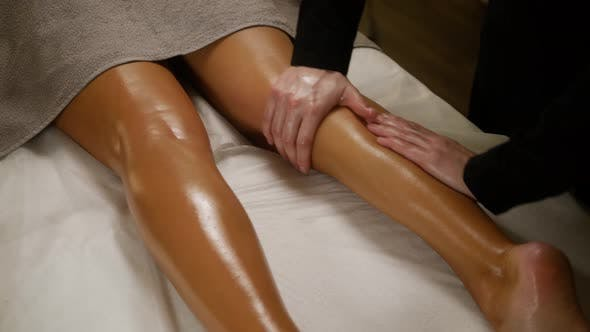Cover Image for Young Beautiful Slim Woman Getting Legs Massage with Oil in Resort Spa Salon. Girl Receiving Body