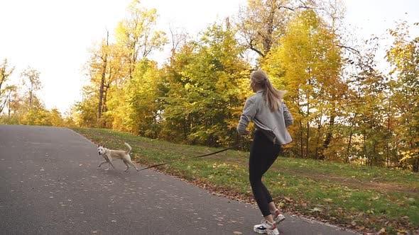 Frau in Sportkleidung ging mit ihrem geliebten Hund im Park spazieren und entschied sich zu joggen