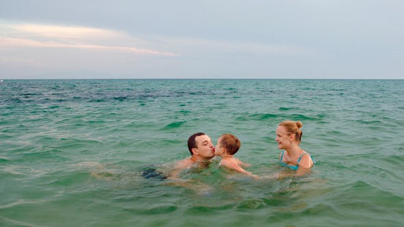 Thumbnail for Happy Family Of Three Playing Ball In Sea