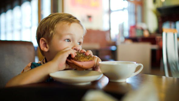 Thumbnail for Little Boy Eating Sandwich In A Cafe