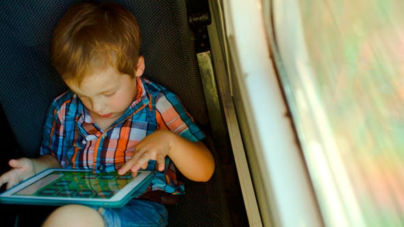 Thumbnail for Boy In Train Using Tablet Computer