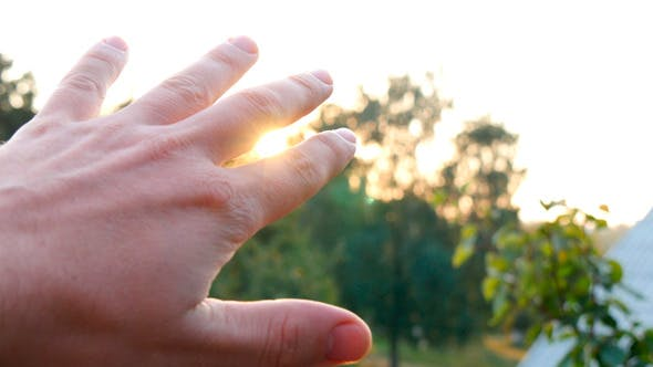 Thumbnail for Man Looking To The Sun Through Fingers