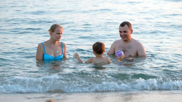 Thumbnail for Parents And Son Playing Ball In Sea