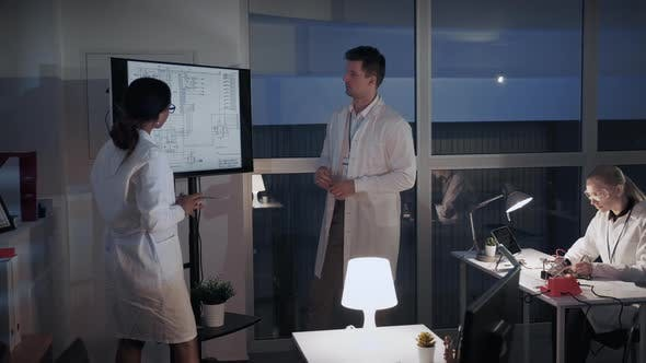 Thumbnail for Chief Engineer Explaining Details of Investigation To His Colleague in Laboratory
