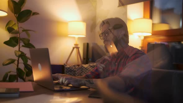 Portrait Of a Man Is Working On Laptop Computer With Glasses At Night. Businessman Working Late At