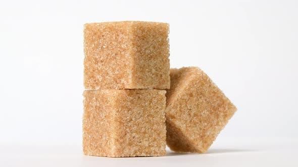 Würfel aus braunem Zucker rotieren auf weißem Hintergrund