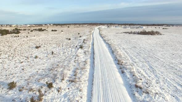 Aerial view of an empty road covered with snow in the nordic forest, Estonia.
