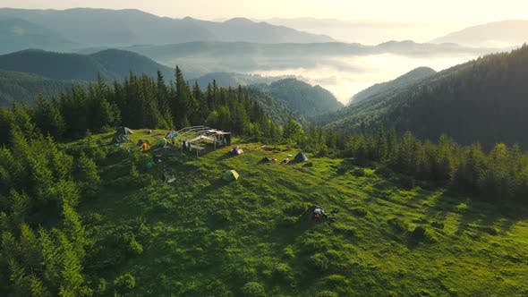 Aerial Flight Over a Tent Camp High in the Mountains at Sunrise