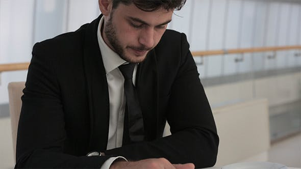 Thumbnail for Businessman is Reading Information On Tablet