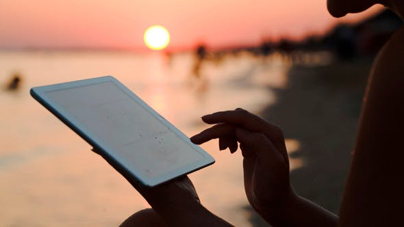 Thumbnail for Girl Working With Tablet Pc On Beach At Sunset