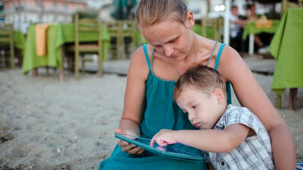 Thumbnail for Mother And Son Using Tablet Pc Near Beach Cafe